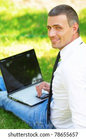 Satisfied young businessman working on laptop with internet wireless