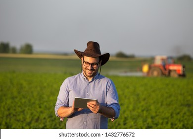 Satisfied young farmer with tablet standing in front of tractor in soybean field