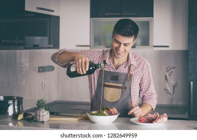 Satisfied young man with apron preparing meat for meal in kitchen at home