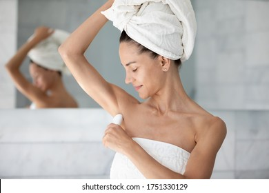 Satisfied young woman with white bath towel on head applying antiperspirant on armpit after shower, standing in modern bathroom, beautiful girl using stick underarm deodorant, morning routine