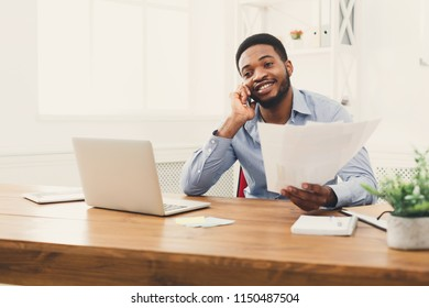 Satisfying call. Happy young black businessman talking on mobile phone and reading report in modern white office, copy space