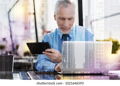 Satisfying results. Calm handsome mature businessman feeling satisfied with the amazing results of his productive work and smiling while sitting with two modern convenient devices