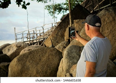 Satoon, Thailand- November 14,2017 ;An adult man enjoyed taking the picture on the nice view of the sea  and the big rocks at Lipe island, southern Thailand.