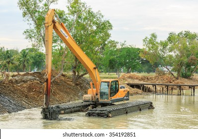 SATTAHIP CHONBURI - DEC,22 : The dirty backhoe working in mud lake for take the mud dam beside the pool site where is renovated new landscape in golf course . THAILAND DEC,22 2015