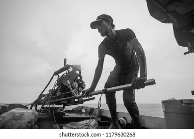 Satun, Thailand - 7 September, 2018 : The opearators of long tail boat work on his engine fail during a trip in Satun, a province in southern Thailand.