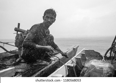 SATUN , THAILAND - SEPTEMBER 7, 2018: Fisherman working on his long tail boat during monsoon season in Satun province, Thailand.