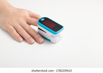 Saturation of hemoglobin of blood with oxygen. Female finger in a pulse oximeter