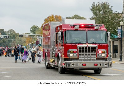 Saturday, October 27, 2018 Coloma Michigan USA; a bright red fire engine heads a parade of costumed kids in an annual Halloween parade