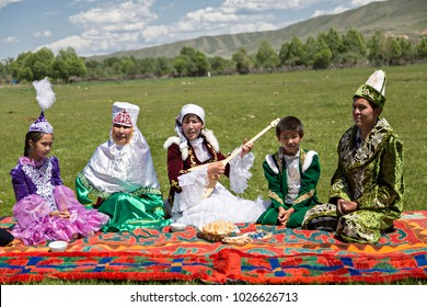 SATY VILLAGE, KAZAKHSTAN - JUNE 3, 2017: Kazakh family sits in the nature with a woman singing and playing local instrument of Dombra, in Saty Village, Kazakhstan.