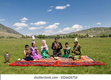 SATY VILLAGE, KAZAKHSTAN - JUNE 3, 2017: Kazakh family pray all together before they start having their picnic lunch in Saty Village, Kazakhstan.