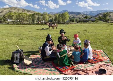 SATY VILLAGE, KAZAKHSTAN - SEPTEMBER 7, 2016: Kazakh family pray all together before they start having their picnic lunch in Saty Village, Kazakhstan.