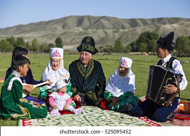SATY VILLAGE, KAZAKHSTAN - SEPTEMBER 7, 2016: Kazakh family sits in the nature and sings all together in Saty Village, Kazakhstan.