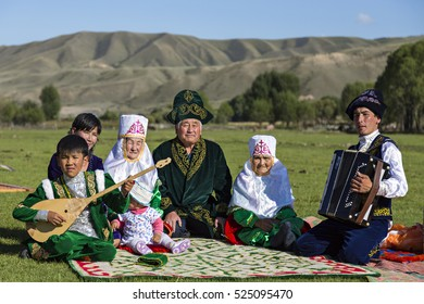 SATY VILLAGE, KAZAKHSTAN - SEPTEMBER 7, 2016: Kazakh family sits in the nature with a man playing acordeon and a kid playing local instrument of Dombra in Saty Village, Kazakhstan.