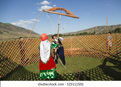 SATY VILLAGE, KAZAKHSTAN - SEPTEMBER 7, 2016: Kazakh nomadic people build a yurt and hold the crown of the dome in Saty Village, Kazakhstan.