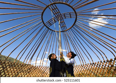SATY VILLAGE, KAZAKHSTAN - SEPTEMBER 7, 2016: Kazakh men build a yurt and hold the crown of the dome in Saty Village, Kazakhstan.