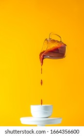 Sauce in glass jar frozen in the air. Pouring homemade DIY natural canned hot tomato sauce from small jar to white ceramic pot. Yellow food art background.