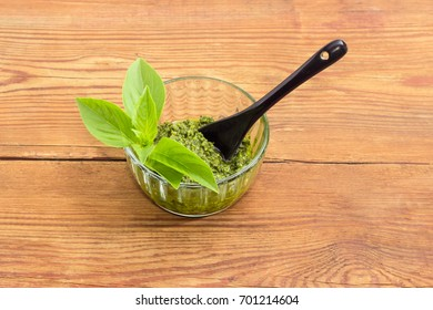 Sauce pesto in the small glass bowl with small black ceramic spoon and decorated with green basil twig on a surface of an old wooden planks