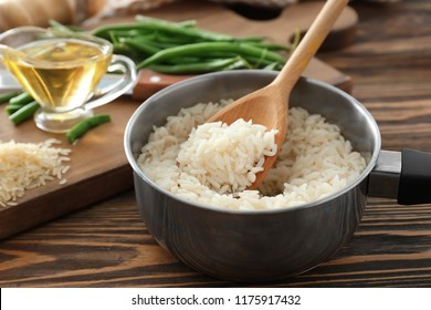 Saucepan with boiled rice on wooden table