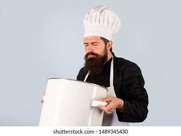 Saucepan, casserole. Cook man in apron holds saucepan in kitchen. Cooking pot. Cookware, dinnerware, kitchenware. Male chef cook holds big pot. Cooking, culinary. Food, profession and people concept.