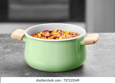 Saucepan with delicious chili con carne on table