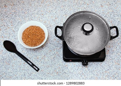 Saucepan on a small electric stove with a steamed lid. On the table there is a bowl with buckwheat groats and a spoon. View from above.
