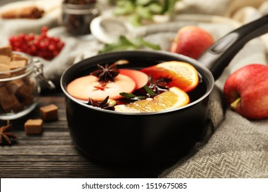 Saucepan with tasty mulled wine on black wooden table