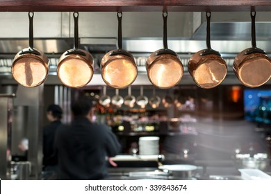 saucepans hanging from a rack in busy kitchen