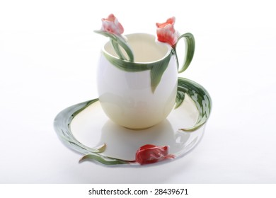 Saucer, cup and spoon decorated with red flower and green color