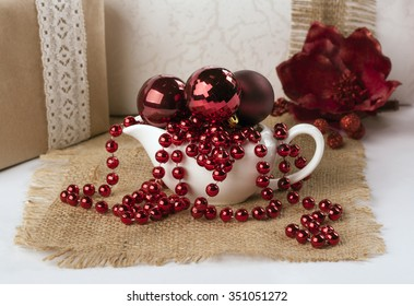 saucers with Christmas balls and beads on the background of Christmas paraphernalia