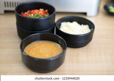 Sauces and condiments in black bowl for Shabu and Sukiyaki
