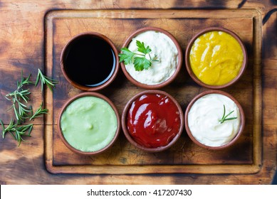 Sauces ketchup, mustard, mayonnaise, wasabi, soy sauce in clay bowls on wooden cutting board