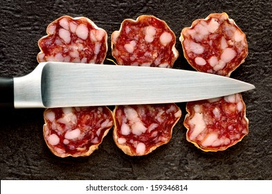 Saucisson slices on a black background with a stainless steel knife resting on top.