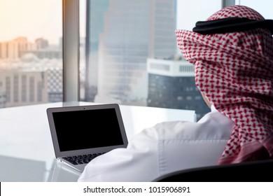 Saudi Arab Man Watching Laptop at Work and Contemplating