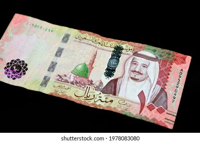 Saudi Arabia 100 riyals banknote, Saudi kingdom one hundred riyals  with the photo of king Salman Bin Abdulaziz and the green dome with The Prophet's Madinah mosque isolated on black background
