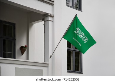 Saudi Arabia flag. Saudi Arabian flag displaying on a pole in front of the house. National flag of Saudi Arabia waving on a home hanging from a pole on a front door of a building.
