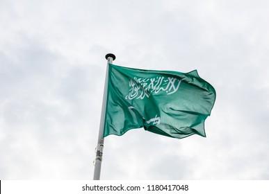 Saudi Arabia flag. Saudi Arabian flag on a pole waving, cloudy sky background
