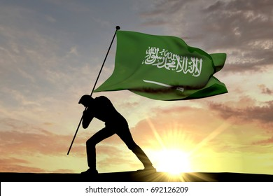 Saudi Arabia flag being pushed into the ground by a male silhouette. 3D Rendering