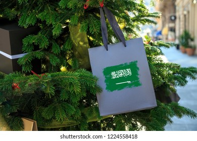 Saudi Arabia flag printed on a Christmas shopping bag. Close up of a gift bag as a decoration on a Xmas tree on a street. New Year or Christmas shopping, local market sale and deals concept.
