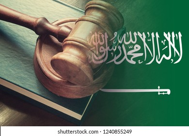 "Saudi Arabia legal and law concept, judge gavel with book on table and Saudi Arabia flag.  The Arabic inscription on the flag: ""There is no god but God: Muhammad is the Messenger of God."""
