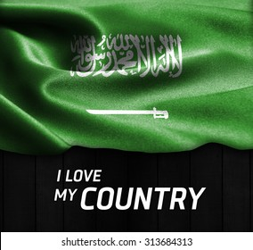 Saudi Arabia waving flag with Text I Love My Country on wood texture background