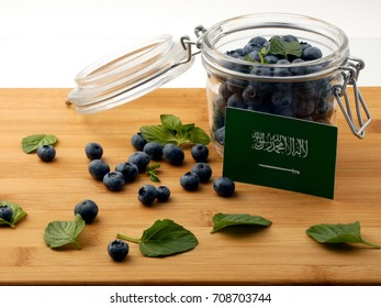 Saudi Arabian flag on a wooden plank with blueberries isolated on white