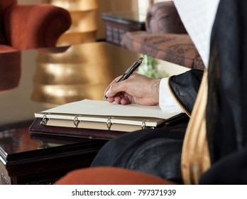 Saudi Arabian Man Hand Writing on A Notebook in a Luxury Home Environment, wearing Saudi Thob, Ghutra and Black Bisht