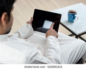 Saudi Arabian Man Using Tablet at Home Environment