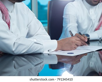 Saudi Businessmen Hands Signing a document, contract