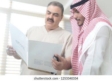 Saudi doctor with gulf patient holds a medical report, Arab man wears a thobe and shimag, Photo in Gulf clinic