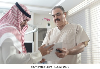 Saudi doctor with gulf patient holds a medical report, gulf man wears a Thobe and Shimag, Photo in Saudi Arabia