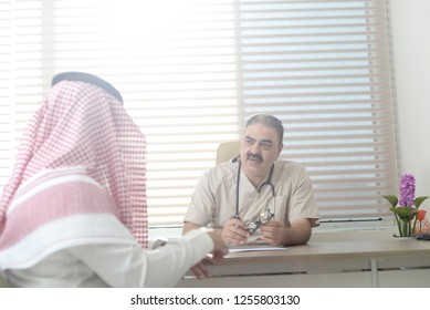 Saudi doctor in office with gulf patient, Arab man wears a shimag, Photo in Gulf clinic