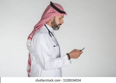 Saudi doctor wearing traditional thobe and Shimagh and looking at his smart phone, on isolated white background ready for cutout and design purposes.