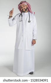 Saudi doctor wearing traditional thobe, Shimagh, medical coat and stethoscope، looking at his smart phone, on isolated white background ready for cutout and design purposes.