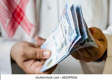 Saudi man holding or paying thousands Saudi Riyal